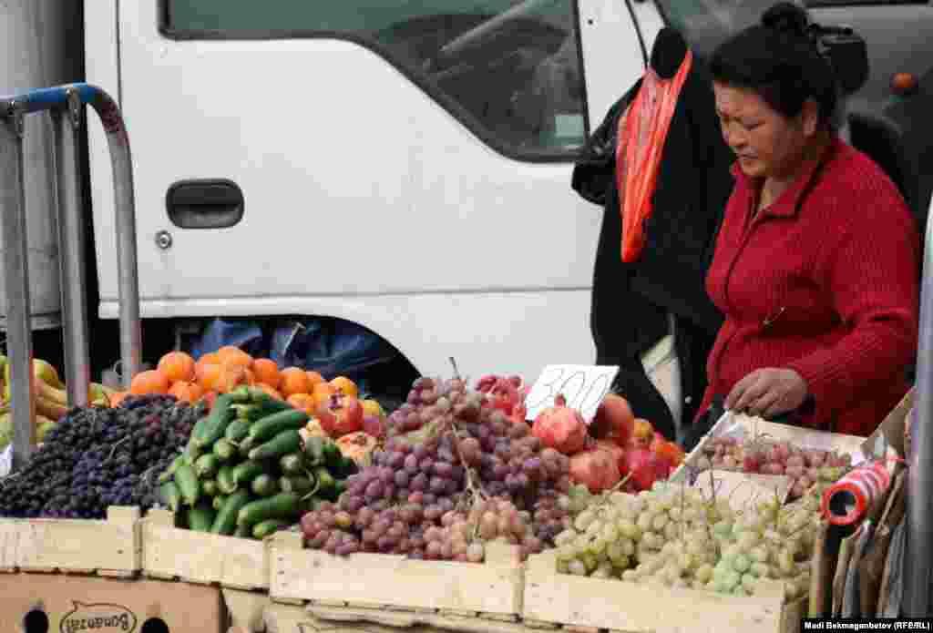 Көк базар сыртында жеміс-жидек сатып тұрған әйел. Алматы, 16 қазан 2012 жыл.