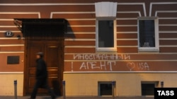 "Graffiti on the building used by the Memorial human rights center in Moscow says ""Foreign agents! I love USA."""