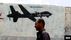 A Yemeni man walks past a graffiti showing a U.S. drone in Sanaa.