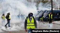 Полиция жанармай салығын көтеруге қарсылық шеруіне қатысушыларға көзден жас ағызатын газ шашты. Париж, 1 желтоқсан 2018 жыл.