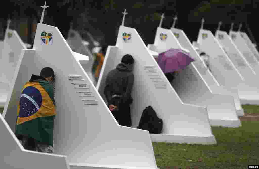 "People confess at confessional booths set up at Quinta da Boa Vista Park as part of World Youth Day in Rio de Janeiro. Pope Francis urged young people to shun the ""ephemeral idols"" of money and pleasure and cherish traditional values to help build a better world. (Reuteres/Sergio Moraes)"