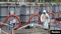 """Рабочий на пострадавшей от цунами АЭС """"Фукусима"""" в Японии. Июнь 2013 года."""