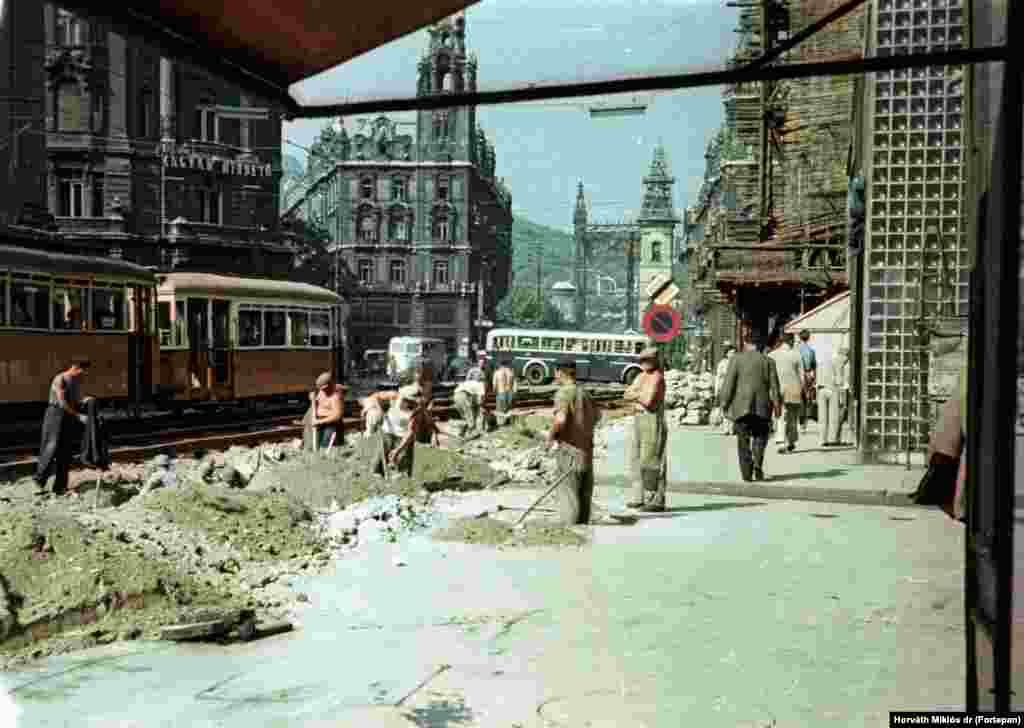 Работы в центре Будапешта. На заднем плане– оригинальная арка моста Эржебет, 1955 год. Мост был снесен и восстановлен через несколько лет после того, как был сделан этот снимок