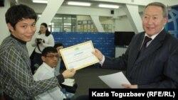 Какимжан Бишманов (справа), руководитель Центра по изучению проблем терроризма и экстремизма в Казахстане, вручает молодому журналисту сертификат об участии в семинаре. Алматы, 31 октября 2013 года.