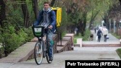 Курьер службы доставки на улице в Алматы, 14 апреля 2020 года.