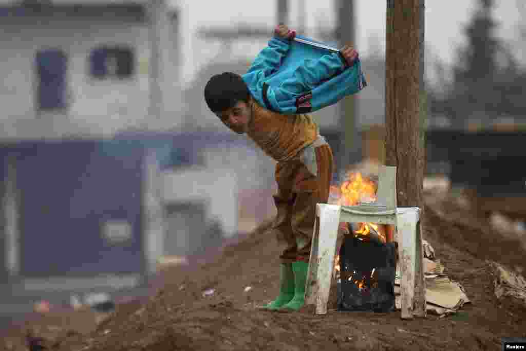 A boy warms himself around a fire in the northern Syrian rebel-held town of Al-Rai. (Reuters/Khalil Ashawi)