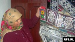 Женщина показывает традиционный в Таджикистане вышитый вручную занавес для ложа новобрачных.