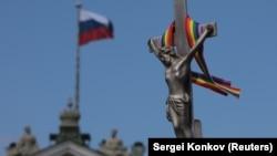 Төбесінде Ресей туы ілінген Эрмитаждың алдындағы крестке таңылған Иса пайғамбардың мүсініне байланған ЛГБТ белгісі – түрлі-түсті таспа.