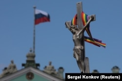 A rainbow-colored ribbon is tied to a crucifix next to a Russian flag fluttering atop the State Hermitage Museum in St. Petersburg last month.