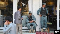 Afghan security personnel secure the front of a damaged building a day after insurgents used it to attack the parliament building in Kabul on April 15.