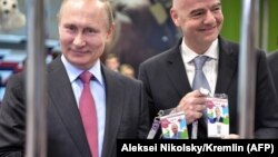 Президент Росії Володимир Путін (л) та президент ФІФА Джанні Інфантіно позують із ідентифікаційними картками вболівальника чемпіонату світу з футболу, Сочі, 3 травня 2018 року
