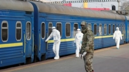 Members of the Ukrainian State Border Guard Service inspect a train carrying Ukrainian citizens evacuated from Russia due to the spread of the coronavirus at the central railway station in Kyiv.
