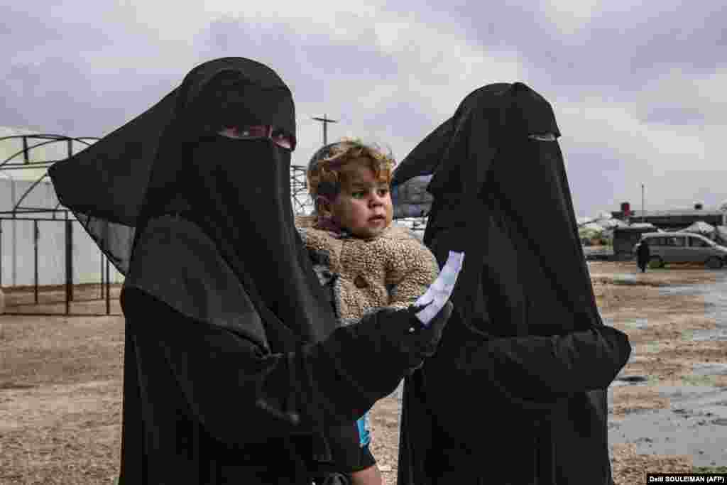 A woman walks carrying a toddler at the Kurdish-run Al-Hol camp for the displaced, where families of Islamic State fighters are held, in northeastern Syria. (AFP/Delil Souleiman)