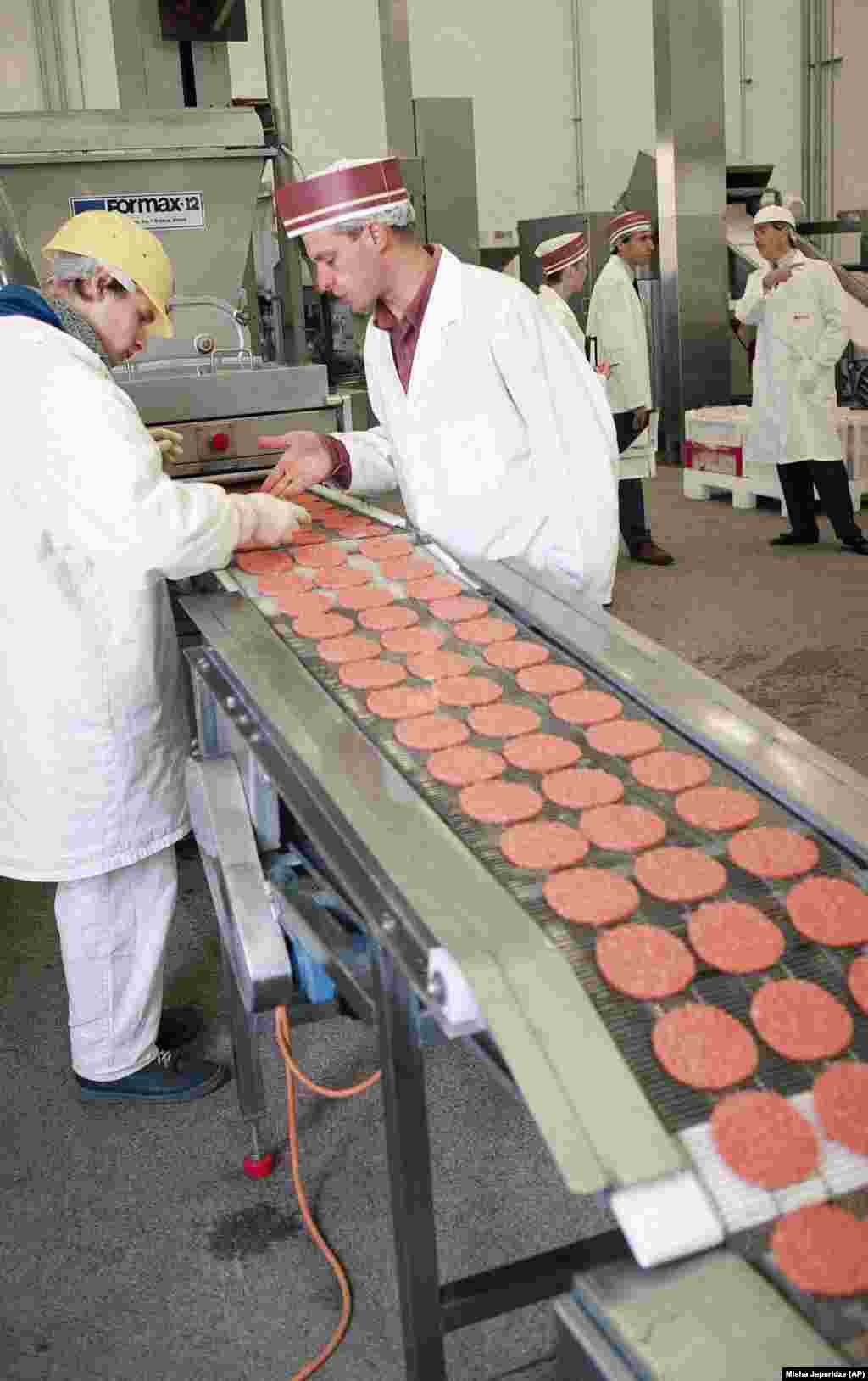 Quality-control inspectors at a McDonald's food-processing plant located in the Moscow suburb of Solntsevo scan a conveyor belt for poorly formed hamburger patties in 1994. Machinery at the plant cranked out 10,000 hamburger patties hourly from beef provided by eight local slaughterhouses.