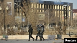Kazakh Interior Ministry troops on December 19, 2011 patrol near burned buildings damaged in the unrest in the town of Zhanaozen three days earlier.