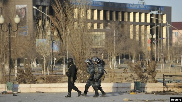 Kazakh Interior Ministry troops on December 19, 2011 patrol near partially burned buildings damaged in the unrest in the town of Zhanaozen three days earlier.