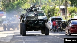 An armored personnel carrier belonging to Philippine government troops drives along a main highway of Pantar town, Lanao Del Norte, as it travels to reinforce Marawi city, where the country's military is battling militants, on May 24.