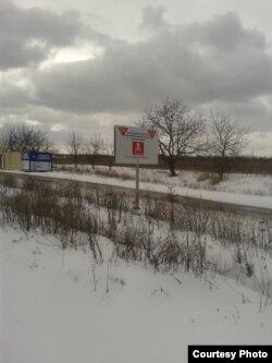 Магазин «Д'юті фрі» угруповання «ДНР», де торгують цигарками на тлі щита з написом-попередженням про міни (фото автора)