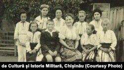 Profesoară cu clasa ei într-o școală rurală; sursa: Centrul de Cultură și Istorie Militară, Chișinău