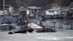 A Russian Navy submarine lies in harbor with a submerged floating dock visible in Sevastopol, Crimea, on December 15.