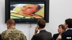 Журналисты и мужчина в военной форме смотрят видео с человеком, которого в министерстве обороны Украины назвали российским военнослужащим, задержанным на востоке Украины. Киев, 18 мая 2015 года.