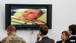 Ukrayna - jurnalistlər və Ukrayna hərbçisi rus əsgəri olduğu deyilən şəxsin videosuna baxırlar, Kiyevdə Ukrayna ordusunun məbuat konfransı, 18 may, 2015