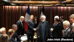 French President Emmanuel Macron shakes hands with Iranian President Hassan Rohani during their meeting on the sidelines of the United Nations General Assembly in New York, September 23, 2019