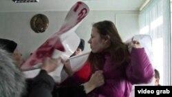 Алена Каваленка адбіваецца ад міліцыянтаў, якія вырываюць плякат зь яе рук. На плякаце напісана: «Свабоду беларусу Сяргею Каваленку»