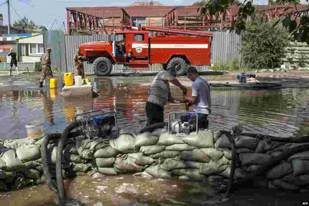 Workers for the Emergency Situations Ministry set up barriers on a flooded street in Khabarovsk on August 21.