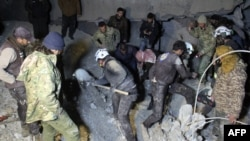 Syrian rescuers dig through rubble following a reported air strike in the village of Al-Jineh in Aleppo Province on March 16.