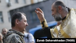 An Orthodox priest blesses pro-Russian separatist commander Igor Strelkov (left) during a religious service in the eastern city of Donetsk on July 10.