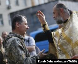 Священик благословляє у Донецьку російського полковника Ігоря Гіркіна (Стрєлкова), одного з колишніх ватажків угруповання «ДНР», яке визнане в Україні терористичним. Липень 2014 року