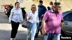 Turkish journalist Nazli Ilicak (center), a well-known commentator and former parliament deputy, is escorted by a police officer and relatives after being detained in Bodrum days after the failed coup in Turkey on July 15.