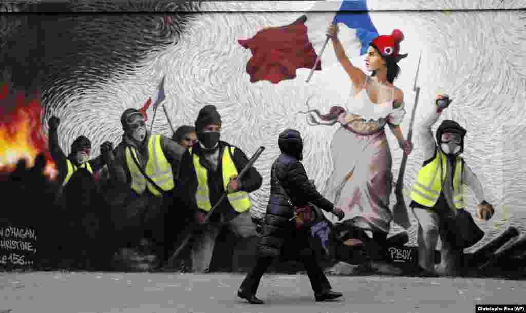 "A woman in Paris passes by a mural inspired by the ""yellow-vest"" protesters. (AP/Christophe Ena)"