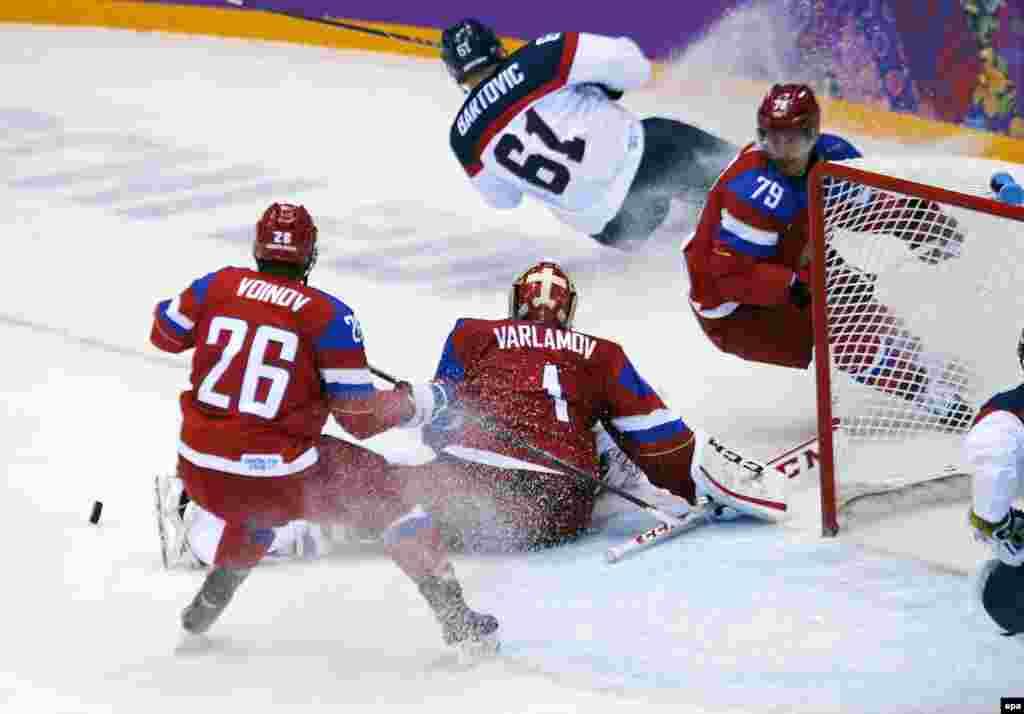 Російський воротар Семен Варламов (2-й л) у протистоянні з Міланом Бартовичем зі Словаччини. Росія виграла цей матч за булітами