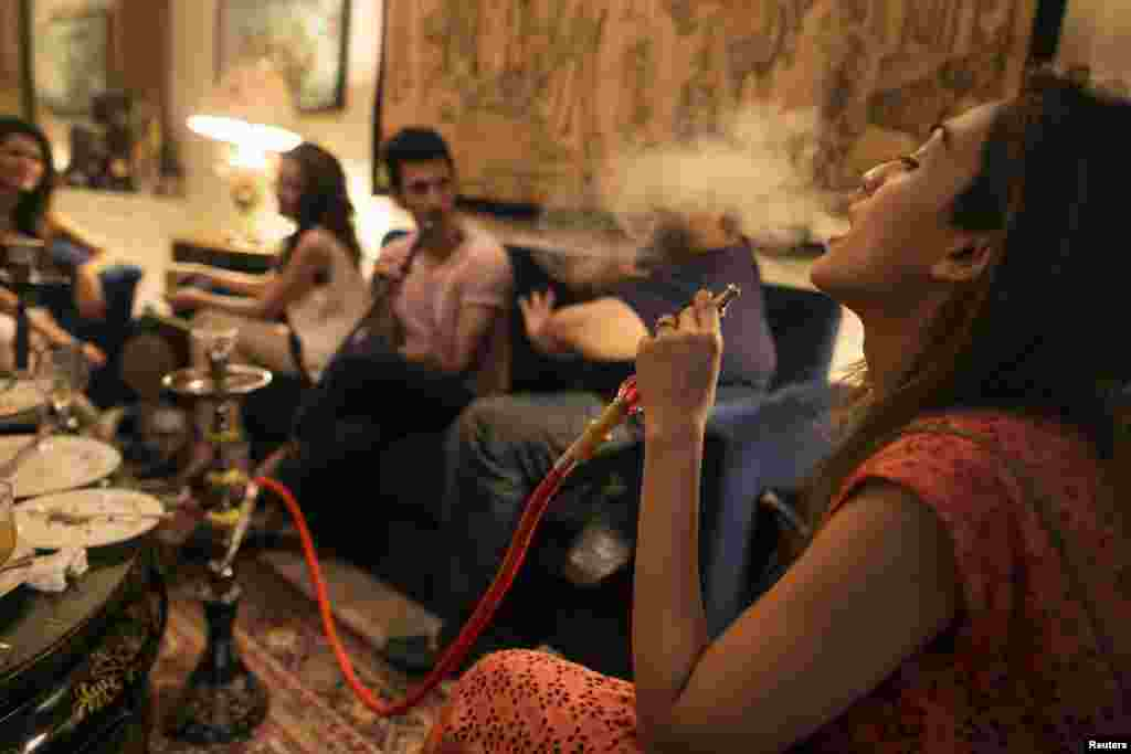 Sarah (right) and her brother, artist Usman Ahmed (second from right), smoke a water pipe, also known as a narghile, as they sit with friends at home in Islamabad.