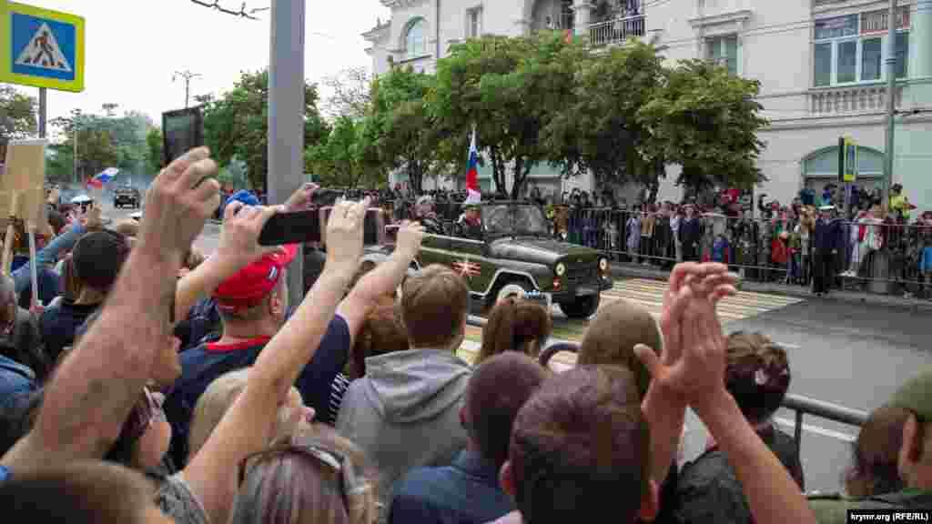 Rusiye bayraqları ile arbiy avtomobiller Aqyarnıñ soqaqlarından keçe
