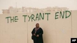 Ливийская женщина ждет транспортировки в Бенгази у ворот с надписью «Конец тирану». 5 июня 2011 года.