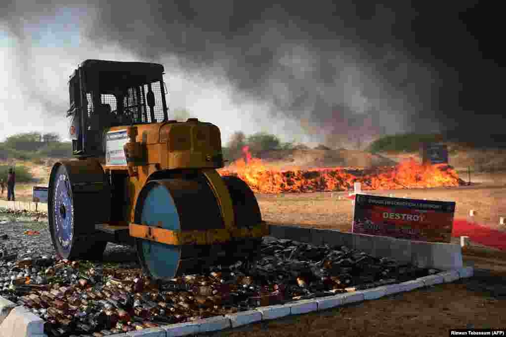 A Pakistani official uses a steamroller to crush bottles of liquor beside burning drugs on the outskirts of Karachi during an event organized by the Pakistan Coast Guards to destroy seized illicit alcohol and drugs smuggled into the country. (AFP/Rizwan Tabassum)