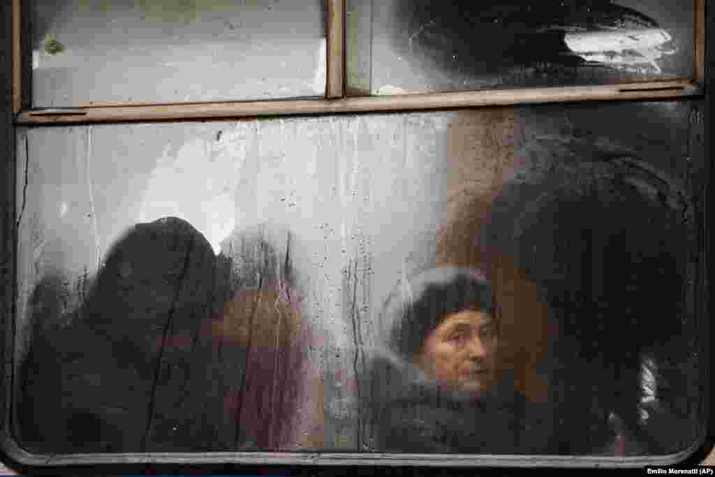 Commuters are seen through the window of a public bus as they travel in central Vinnytsia, Ukraine. (AP/Emilio Morenatti)