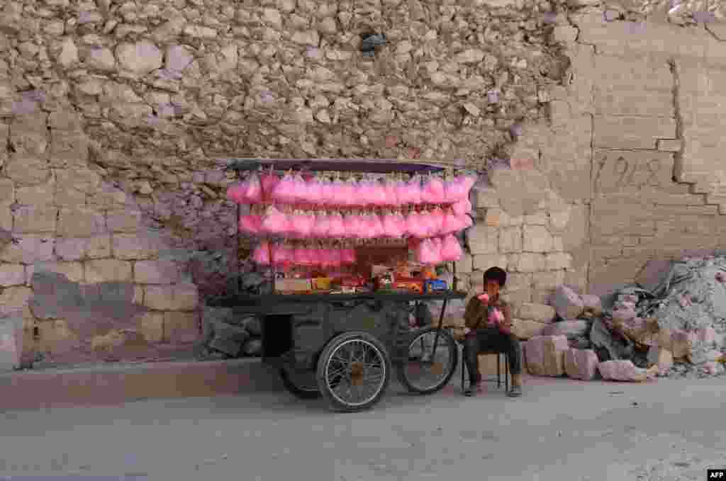 A Syrian child eats cotton candy while selling it on a street cart in the city of Al-Bab in the northern Aleppo Province on May 15. (AFP/Zein Al Rifai)