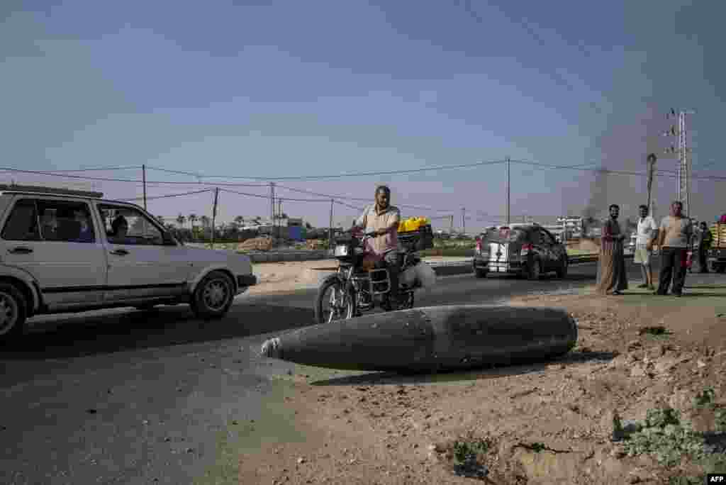 Palestinian onlookers and motorists pause to inspect an Israeli army bomb as it lies unexploded on the road that links northern and southern Gaza. (AFP/Marco Longari)