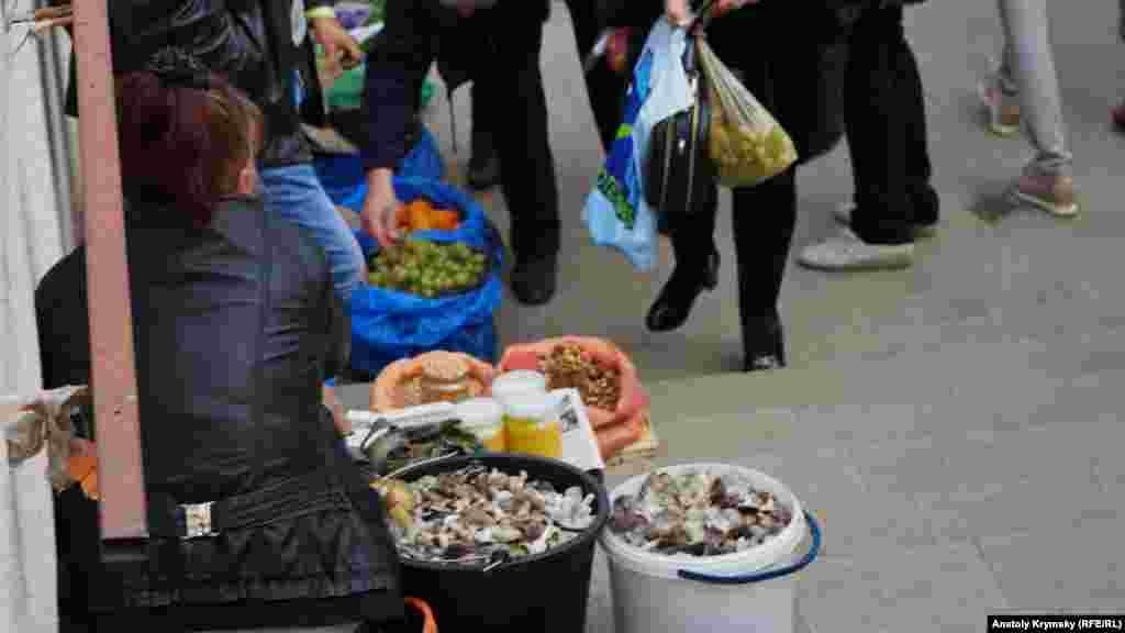 В подземном переходе на площади Куйбышева в Симферополе женщина продает два ведра «мышат», или серой рядовки