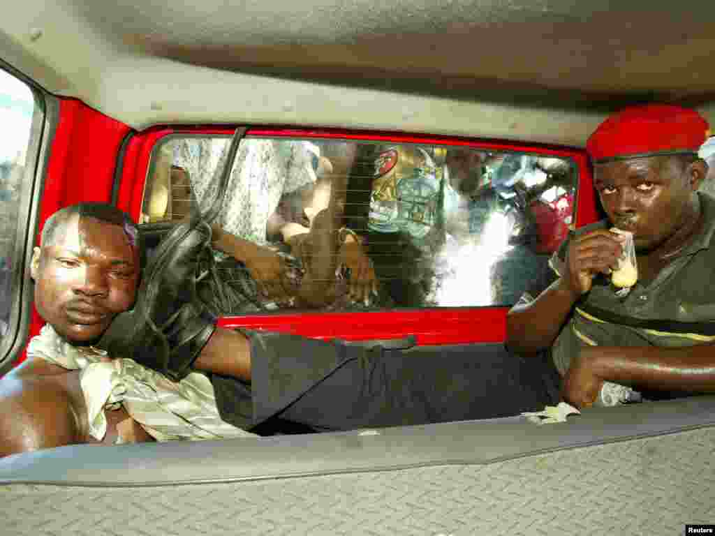 A suspected assassin for exiled Hatian president Jean Bertrand Aristide's Lavalas party being held in a car in Petit Goave, Haiti March 3, 2004. REUTERS/Daniel Aguilar
