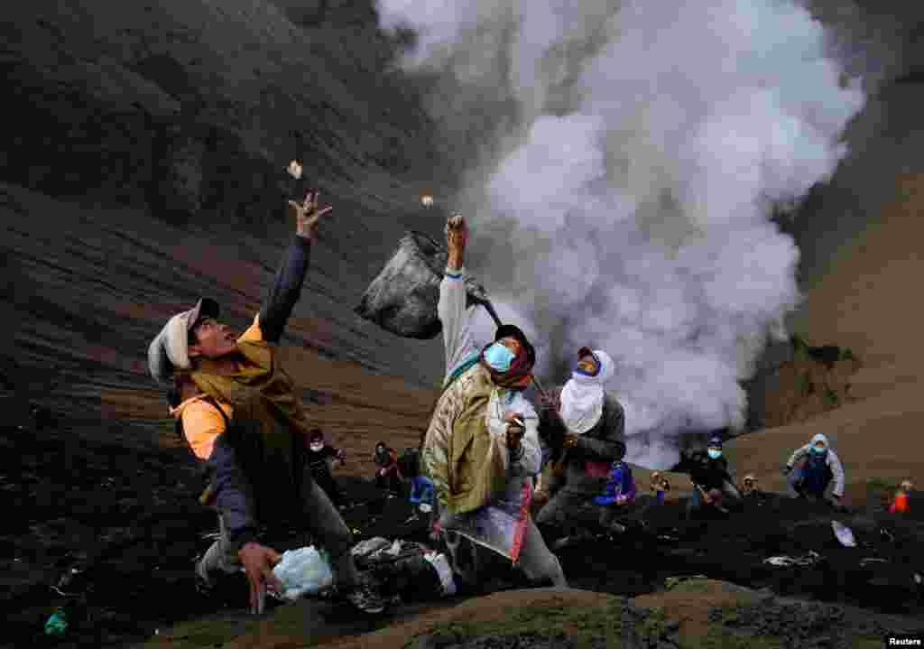 Probolinggo, Indonezia: oba adamlary Bromo wulkanynyň golaýýynda wulkandan göterilýän tüsse we kül arasynda gaýmalaýan pullary tutmaga çalyşýar. Yrymçy adamlar Kaskada dabarasynda bu wulkana pul we mal taşlaýarlar. (Reuters/Beawiharta)