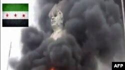 Pamjet tregojnë statujën e Hafez al-Assadit të kapur në flakë.