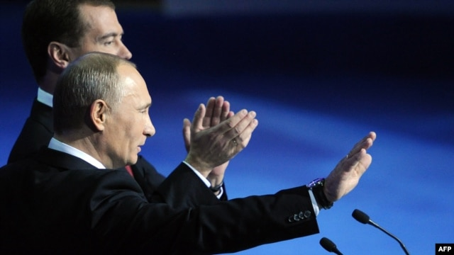 Dmitry Medvedev (back) and Vladimir Putin wave to delegates at a United Russia congress in Moscow on November 27.