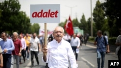 "Republican People's Party leader Kemal Kilicdaroglu walks with a placard reading ""Justice"" during a protest march in Ankara in June."