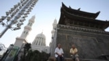 CHINA -- Residents at rest outside a mosque with Chinese characteristics in Yining, western China's Xinjiang province, August 8, 2008