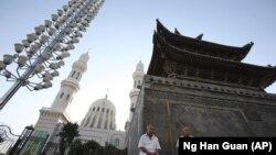 Қытайлық стильге бейімделген мешіт алдында отырған тұрғындар. Құлжа қаласы. Көрнекі сурет.